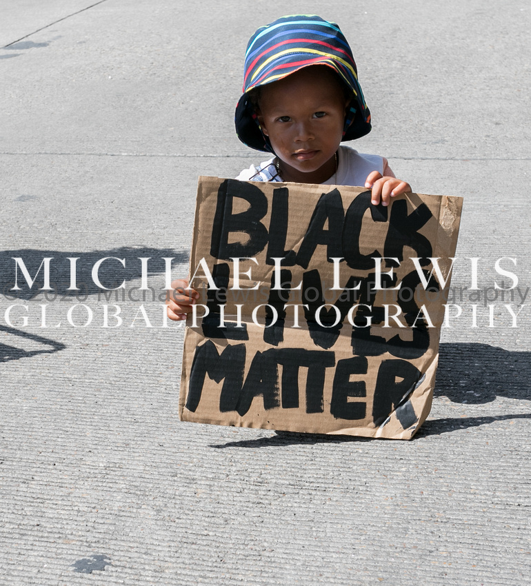 A beautiful innocent Black child holding a Black Lives Matter sign. -2020.